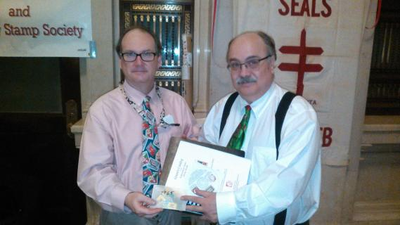 Matthew A. White, PhD, Director of Education and Visitor Services Smithsonian National Postal Museum (Washington DC) receiving Christmas Seal Collection from CS&CSS member Lloyd Thrower